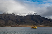 A ship sails through high snow-capped mountains, Spitsbergen, Norway, Europe