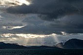 Landscape photo of the sun bursting through openings in the clouds to shine on a barren, snowy scene, Ny-Ålesund, Spitsbergen, Norway, Europe