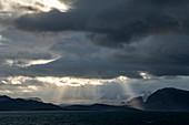 Landschaftsaufnahme der Sonne, die durch Wolkenöffnungen bricht, um auf eine karge, schneebedeckte Szene zu scheinen, Ny-Ålesund, Spitzbergen, Norwegen, Europa