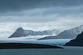 Graphic scene of rugged mountains and a long, wide glacier that stretches to the sea, Signehamna, Land Albert I, Spitsbergen, Norway, Europe