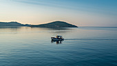 Fishing boat goes out to sea early in the morning, Skiathos, Greece