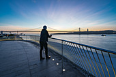 Tourist looks out over the Tagus and Ponte 25 de Abril, Lisbon, Portugal early in the morning