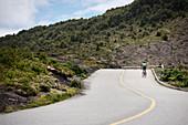 Racing cyclist on road to summit of Osorno volcano, Region de los Lagos, Chile, South America