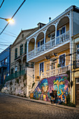 Two young women examine street art on a historic building in the streets of Valparaiso, Chile, South America