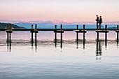 Blick auf einen Steg am Starnberger See bei Sonnenuntergang, im Hintergund die Alpen, Starnberg, Bayern, Europa
