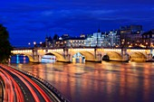 France, Paris, area listed as World Heritage by UNESCO, the Pont Neuf bridge spans across the Seine at night, lights of driving cars can be seen on the left foreground