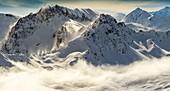 France, Savoie, Beaufortain, Hauteluce, mist in a snowy landscape at sunset