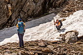 Wanderin skilfully slips down old snow, Trekking del Laghetti Alpini, Ticino, Switzerland