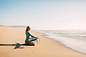 Woman kneeling holding surfboard on beach