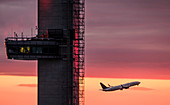 Airplane flying past control tower at sunset
