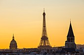 France, Paris, area listed as World Heritage by UNESCO, the illuminated Eiffel Tower (© SETE illuminations Pierre Bideau), the dome of the Hotel des Invalides and the bell tower of the Saint Germain des Pres with the roofs of Paris at sunset