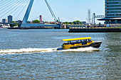 A taxi boat travels on the New Meuse to the Kop van Zuid district. The Erasmus Bridge can be seen in the background. Rotterdam, The Netherlands, June 2020