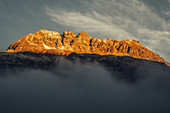 Mountains on Lake Silvaplana in fog at sunrise, in the Upper Engadine, St. Moritz in the Engadine, Switzerland