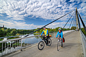 Man and woman ride a bike over the Charbonniere-les-Bains bridge, Danube bike path, Bad Abbach, Lower Bavaria, Bavaria, Germany