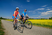Man and woman cycling past rape field, Danube Cycle Path, Lower Bavaria, Bavaria, Germany