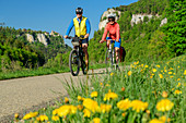 Man and woman ride a bike through the Upper Danube Valley, rocks in the background, near Beuron, Upper Danube Valley, Danube Cycle Path, Baden-Württemberg, Germany