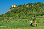 Man and woman ride a bike through the Upper Danube Valley, Werenwag Castle in the background, Upper Danube Valley, Danube Cycle Path, Baden-Württemberg, Germany
