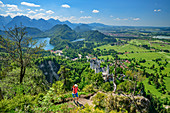 Woman hiking hikes to Tegelberg, Tannheim Mountains, Alpsee and Neuschwanstein Castle in the background, Tegelberg, Ammergau Alps, Swabia, Bavaria, Germany