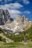 Woman hiking hikes to Geiselsteinjoch, crow and forked cremator in the background, Ammergau Alps, Swabia, Bavaria, Germany