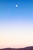 Aufgehender Mond über einem Dorf im Odenwald, Hessen, Deutschland