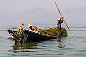 Fischer mit Stöcken auf kleinem Boot am Inle See, Heho, Myanmar