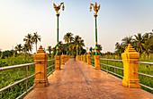Path with orange stone pillars through nature in the evening light on Koh Kret, Bangkok, Thailand