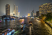 View from Taksin Bridge on boats and skyscrapers at night, Bangkok, Thailand