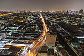 View over apartment buildings and skyline in Upper Sukhumvit from skyscraper at night, Bangkok, Thailand