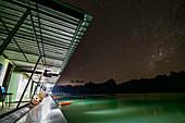 Sicht über Steg mit Bungalows (Khao Sok Smiley Lake House) bei Nacht mit Milchstraße, Ratchaprapha See, Khao Sok Nationalpark, Thailand
