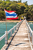 Long jetty into the sea with Thailand flag at Wat Koh Phayam temple, Koh Phayam. Thailand