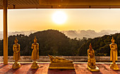 Buddha statues at sunset on Tiger Cave Mountain, Tiger Cave Temple, Krabi Town, Thailand