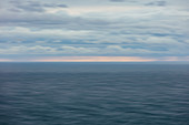 Blurred motion abstract of ocean, horizon and stormy sky at dusk