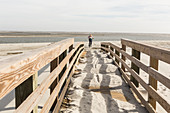 teen girl on her bike crossing bridge to the beach, St. Simon's Island, Georgia