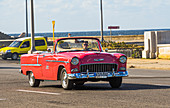 Red classic car on the Malecon - promenade by the water. Old Havana, Cuba