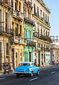 Vintage car drives through Cuban street with old, colorful colonial-style house facades, Old Havana, Cuba