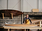 Portrait of man standing in front of hand made wooden paddleboard in workshop
