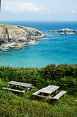 Wooden picnic tables on a cliff on the Pembrokeshire Coast, Wales, UK.