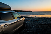 Car parked on a beach on the Pembrokeshire Coast, Wales, UK at sunset.
