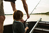 A five year old boy fishing from a boat on the Zambezi River, Botswana