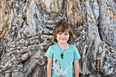 A five year old boy posing against trunk of a large Baobab tree