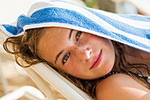 13 year old girl reclining in beach chair with towel on her head