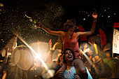 Revellers at an open air concert, smiling man carrying woman on his shoulders, arms outstretched, holding beer bottle.