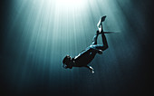Underwater view of diver wearing wet suit and flippers, sunlight filtering through from above.