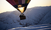 People in a hot air balloon mid air over a snow covered mountain.