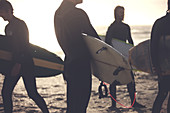 Four men wearing wetsuits standing on a sandy beach, carrying surfboards.
