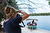 A woman using her camera, taking photographs of a boat with passengers on the Zambezi River, Botswana