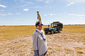 adult woman with Meerkat on her head, Kalahari Desert, Makgadikgadi Salt Pans, Botswana