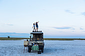 A brother and sister standing on top of a safari vehicle at dusk in a salt pan landscape