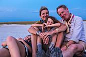 smiling family on top of safari vehicle, Nxai Pan, Botswana