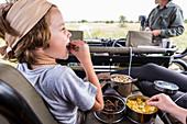 6 year old boy eating snacks in safari vehicle, Botswana